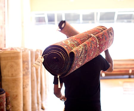 Worker Carrying Oriental Rug